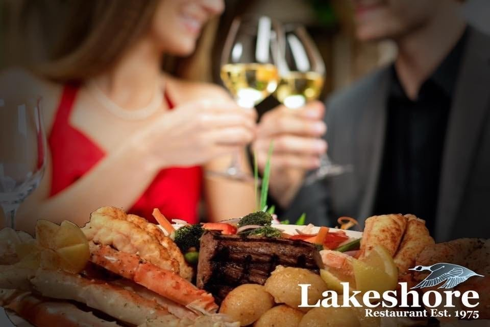 Lakeshore Restaurant Est. 1975. Surf and turf platter in front of a couple enjoying wine